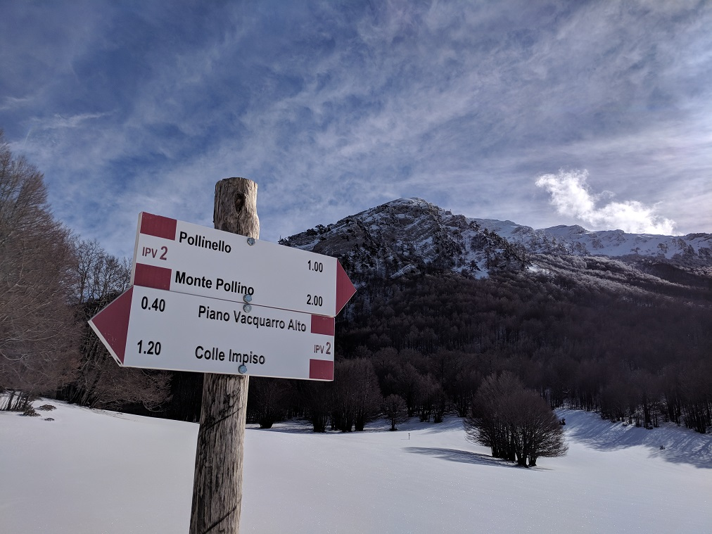 Sign to Pollino at the base of the mountain with a false peak hiding the true peak.